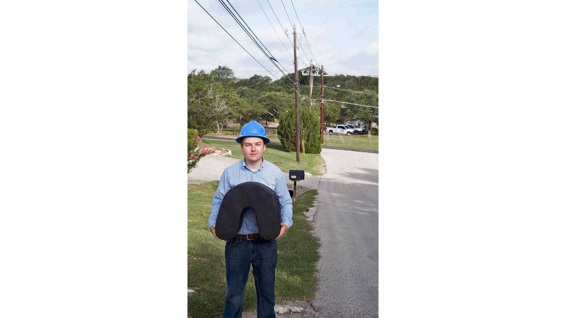 An engineer holds the custom spool-free cable coil used for aerial fiber deployment