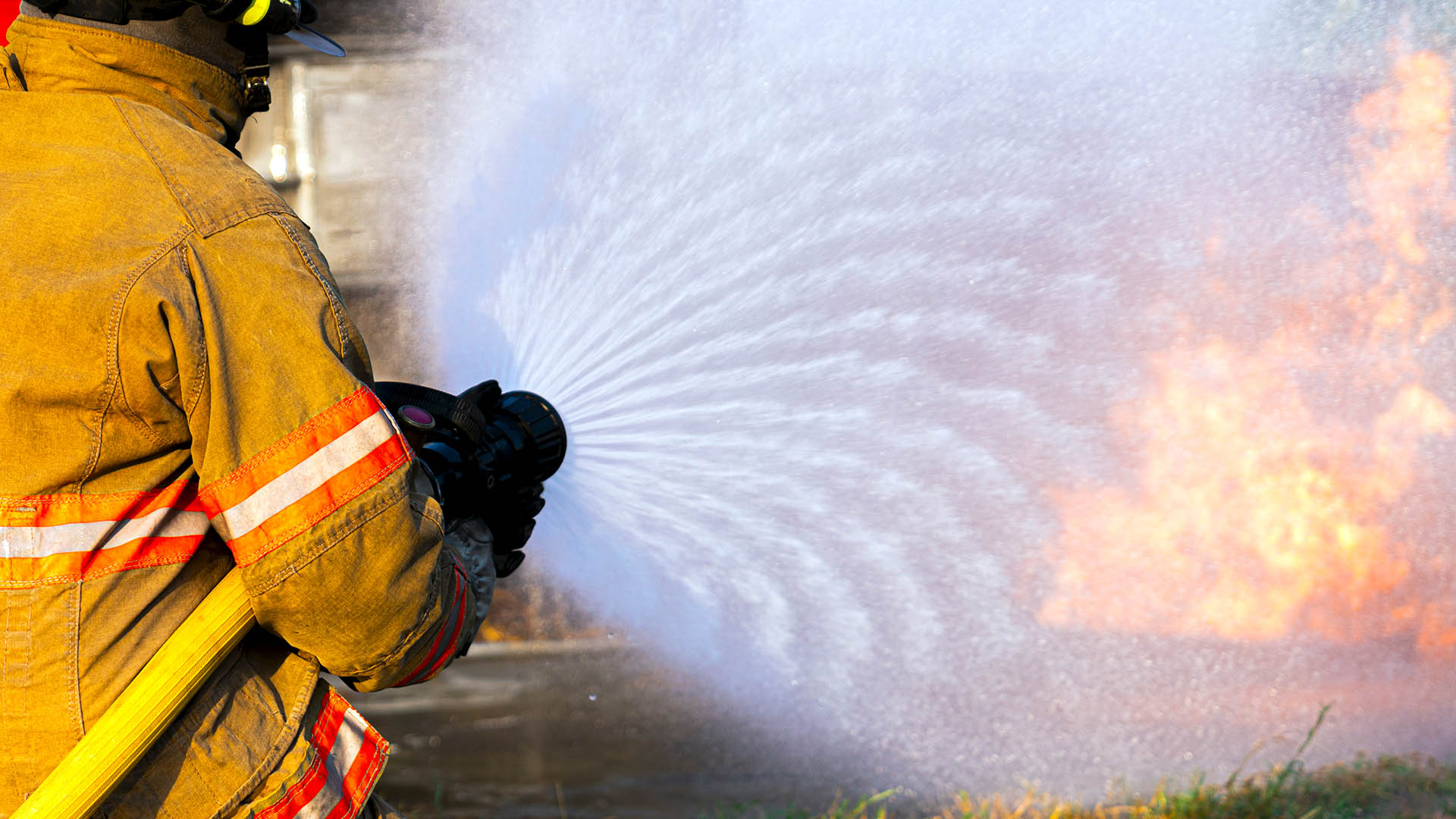 Network hose: Managing uncertain network demand. Image shows Rear View Of Firefighter high pressure spraying water to stop fire.